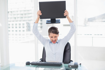 Angry classy brown haired businesswoman throwing her computer sc
