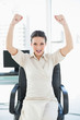 Cheering stylish brunette businesswoman raising her arms