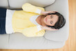Calm casual brunette in yellow cardigan listening to music with