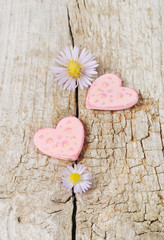 Two pink hearts on wooden background