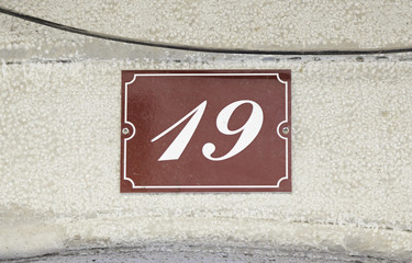 Metal plate with the number nineteen