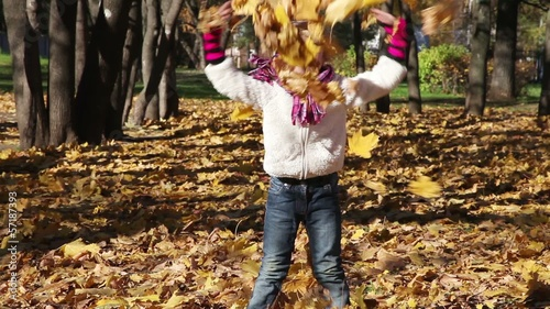 A four years old girl throws autumn leaves and laughs
