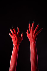Red demonic hands with black nails, real body-art