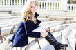 Pretty blonde girl sitting in the bench wearing in  coat