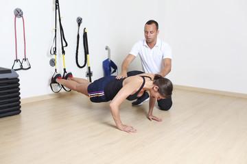 Frau beim Schlingentraining mit Trainer