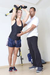 Woman doing trx training with therapist