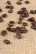 Coffee beans on burlap background close up