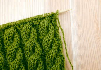 Green cable knitting stitch on the needle
