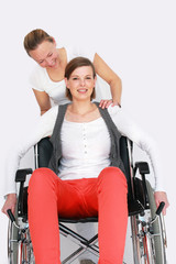 Krankenpflegerin mit Rollstuhlfahrerin