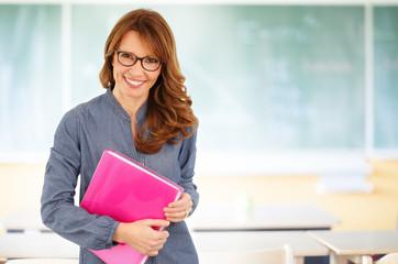 Smiling teacher in front of the blackboard