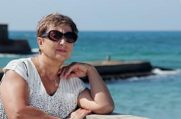 Happy mature woman walking near the sea