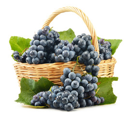 Wicker basket full of fresh red grapes isolated on white