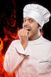 Chef bitting nails against fire in background
