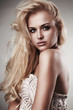 Beautiful blond woman in dress.passion.gray background