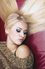beautiful blond woman laying on a red leather.hair style