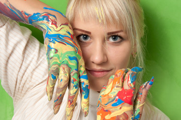 Portrait of a young woman with hands in fresh paint
