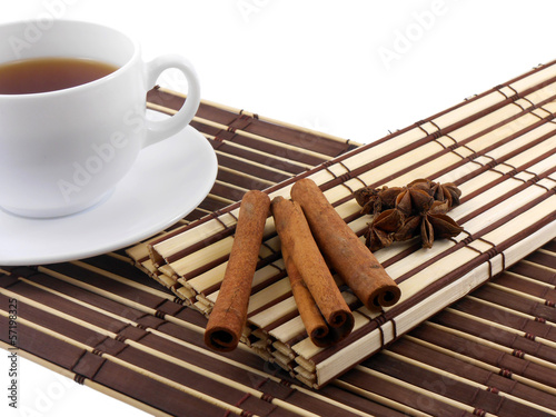 tea cup with cinnamon and star anis on bamboo background