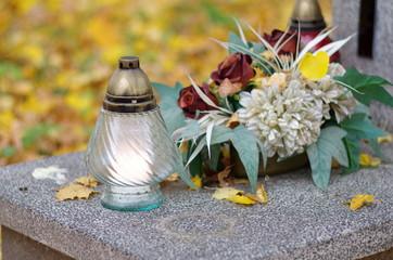 Znicz na grobie w jesiennej oprawie Święto Zmarłych