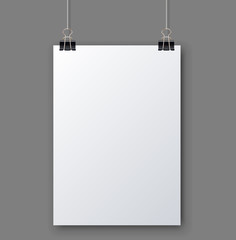 Blank white page hanging against grey wall
