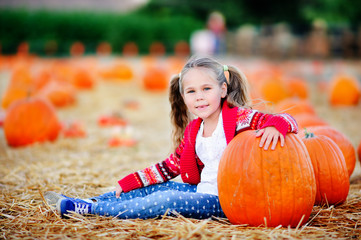 Happy toddler girl picking a pumpkin for Halloween