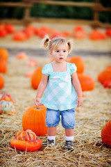 Happy little girl picking a pumpkin for Halloween