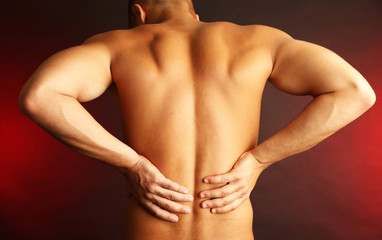 Young man with back pain on dark background