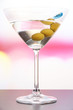 Martini with green olives on table in bar