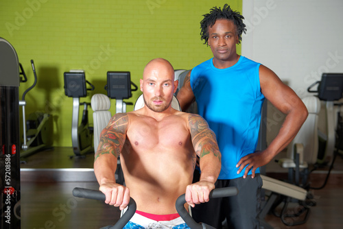 Man with trainer in gym
