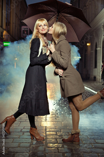 Blonde girl kissing her friend's chick