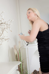 Woman spraying her hair with hairspray