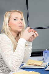 Thoughtful woman eating her breakfast