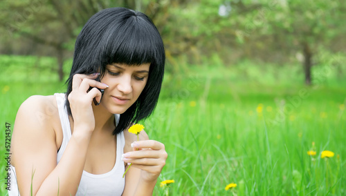 Girl with dandelion talking on mobile