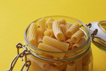 Raw rigatoni pasta on a glass jar