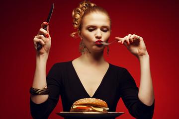 Portrait of fashionable model eating big burger