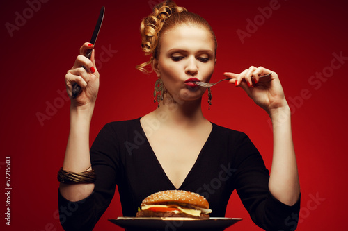 Portrait of fashionable model eating big burger