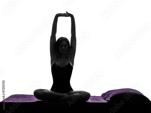 woman in bed waking up stretching arms silhouette