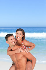 Handsome man having wife a piggyback on the beach
