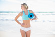 Cute blonde woman in sportswear holding an exercise mat
