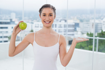 Cheerful sporty brunette holding green healthy apple