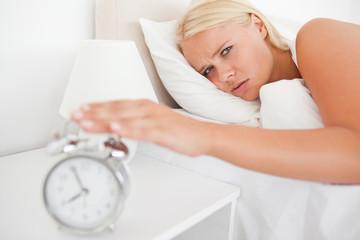 Tired woman awaken by an alarmclock