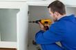 Young handyman fixing a door
