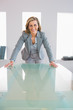 Happy businesswoman standing in front of a desk