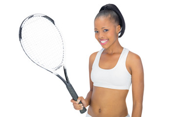 Smiling woman in sportswear holding tennis racket