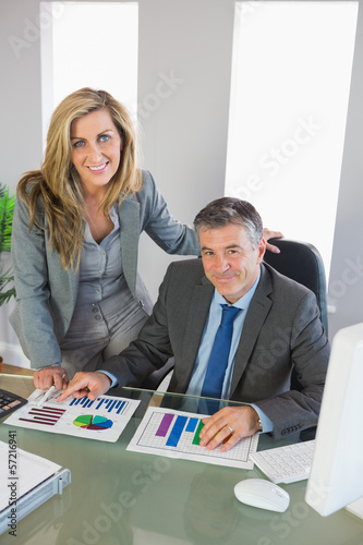Businesspeople smiling at camera studying figures