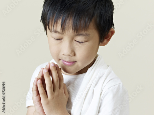 little asian boy praying with clasped hands
