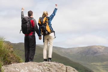 Excited couple reaching the top of their hike and cheering