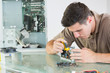 Handsome serious computer engineer repairing hardware with plier