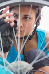 Focused woman adjusting her spokes on bike wheel