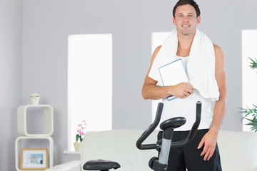 Smiling sporty man standing behind exercise bike holding tablet