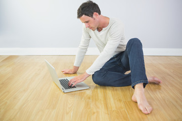 Casual calm man sitting on floor using laptop